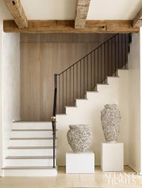 Wood paneling along the three-story staircase adds ...