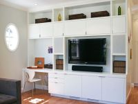 SIMPLE A modern white entertainment center lines one wall ...