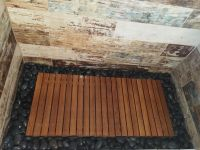 Teak wood shower floor surrounded by river rock, walls ...