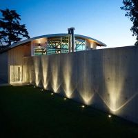 Uplighting the concrete wall for dramatic effect.   Modern ...
