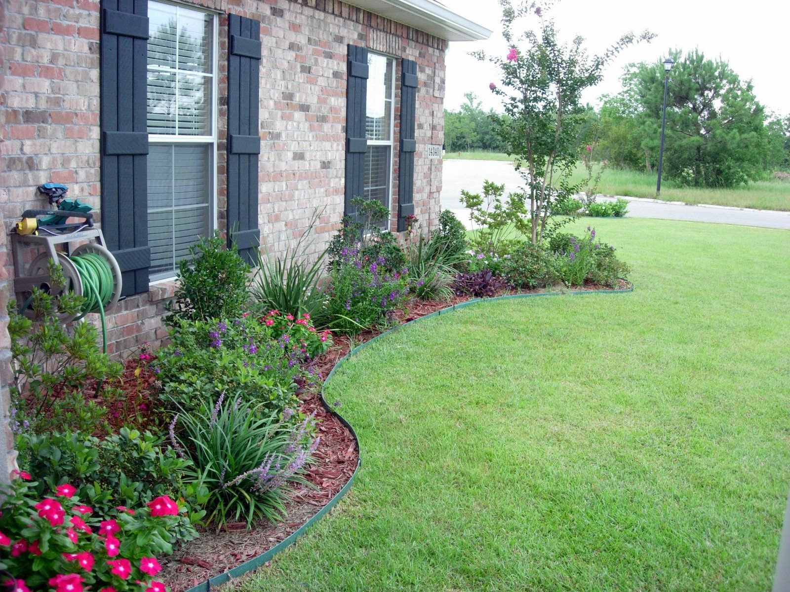 Landscape flower beds in front of house use shrubs small trees to form the skeletal struct ure of your