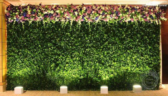 A greenery wall with floral accents.