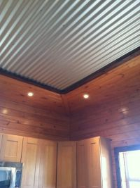 Interesting tin ceiling framed by tounge and groove pine ...