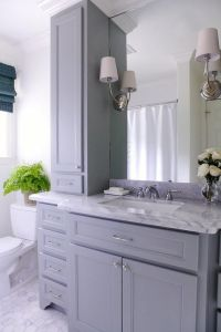 Lovely bathroom features a gray vanity paired with a grey ...