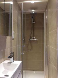 The en suite shower room is fully tiled in dark cream ...
