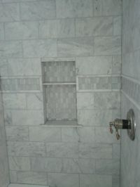 This picture shows a marble tile shower with an accent ...