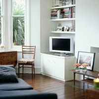 Living room with wood floor, sofa and white TV unit ...