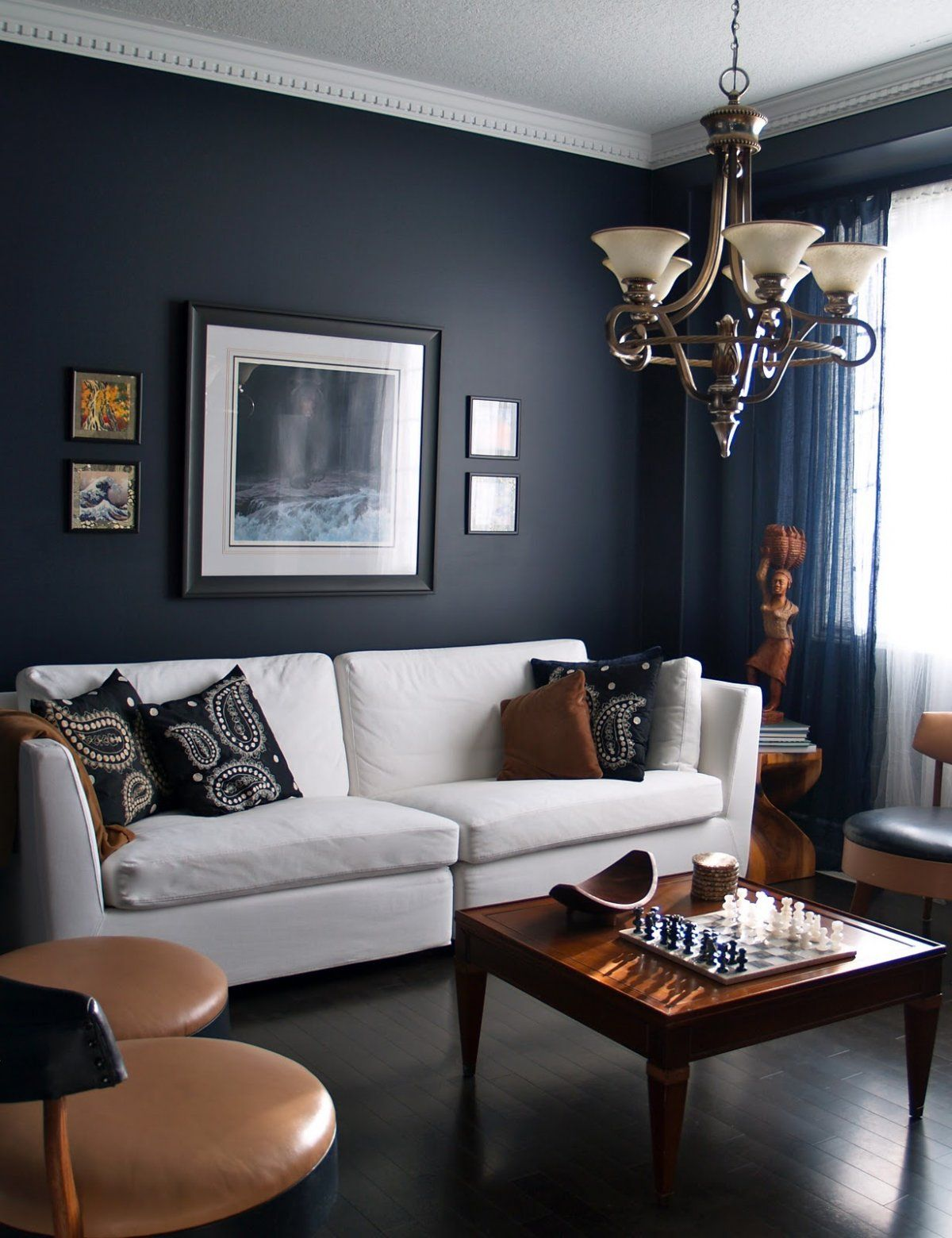 Dark and white themed navy living room ideas with classic white fabric sofa furniture on the black wood flooring and natural brown wood square shaped table