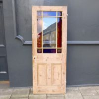Reclaimed Victorian door has richly coloured blue and red ...