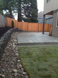 Concrete patio, river rock border with drainage and lawn ...