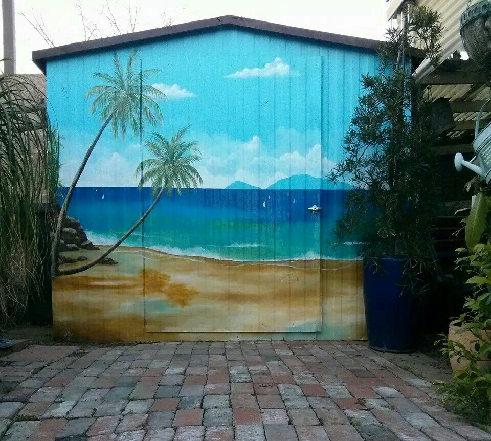 Outdoor Garden shed painted with beach scenery. Shed