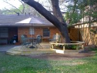 Small backyard deck under the big tree with round table ...