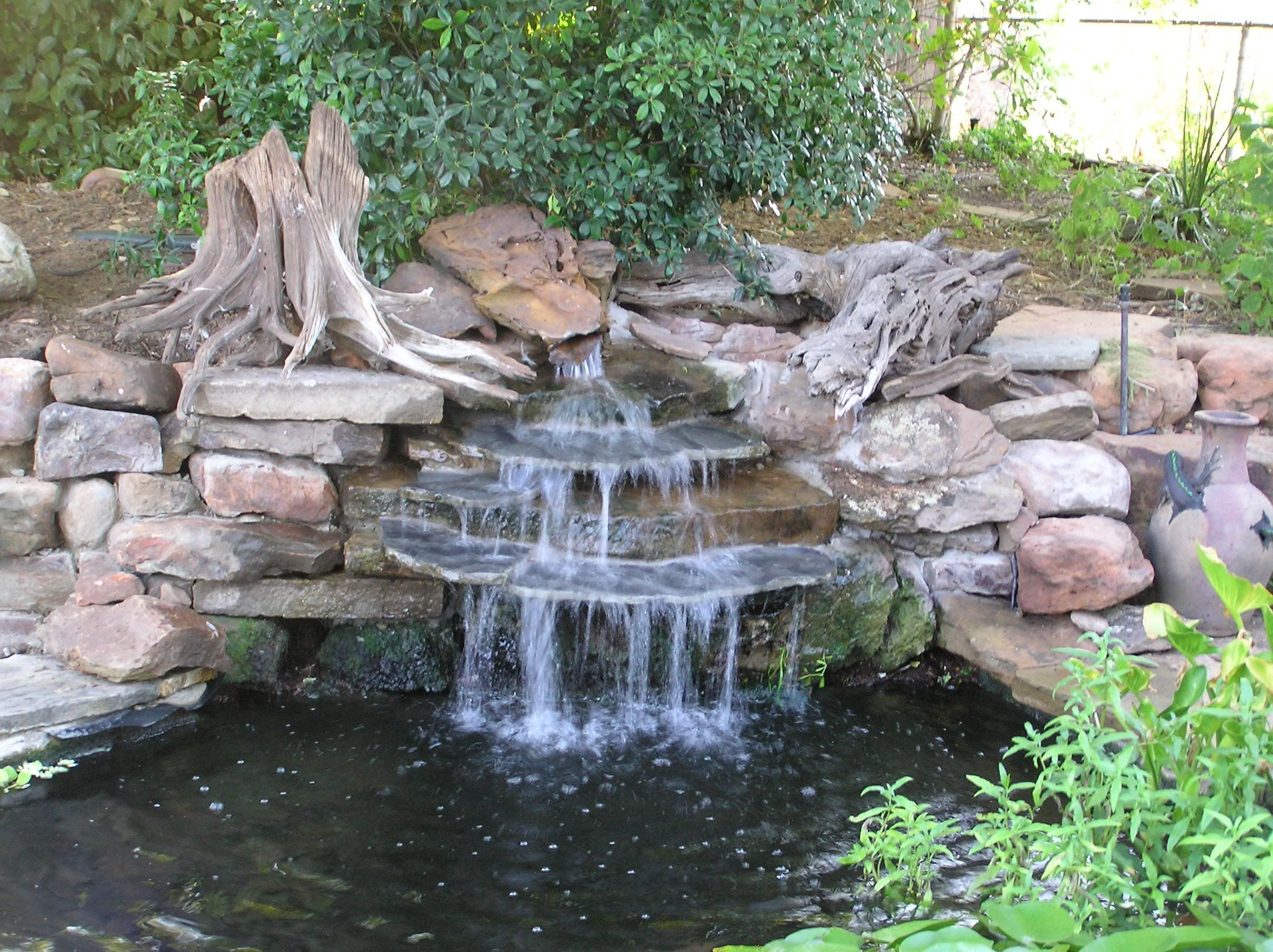small diy ponds with waterfall and stone border in the corner backyard