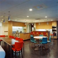 A simple breakroom setup with colorful chairs.