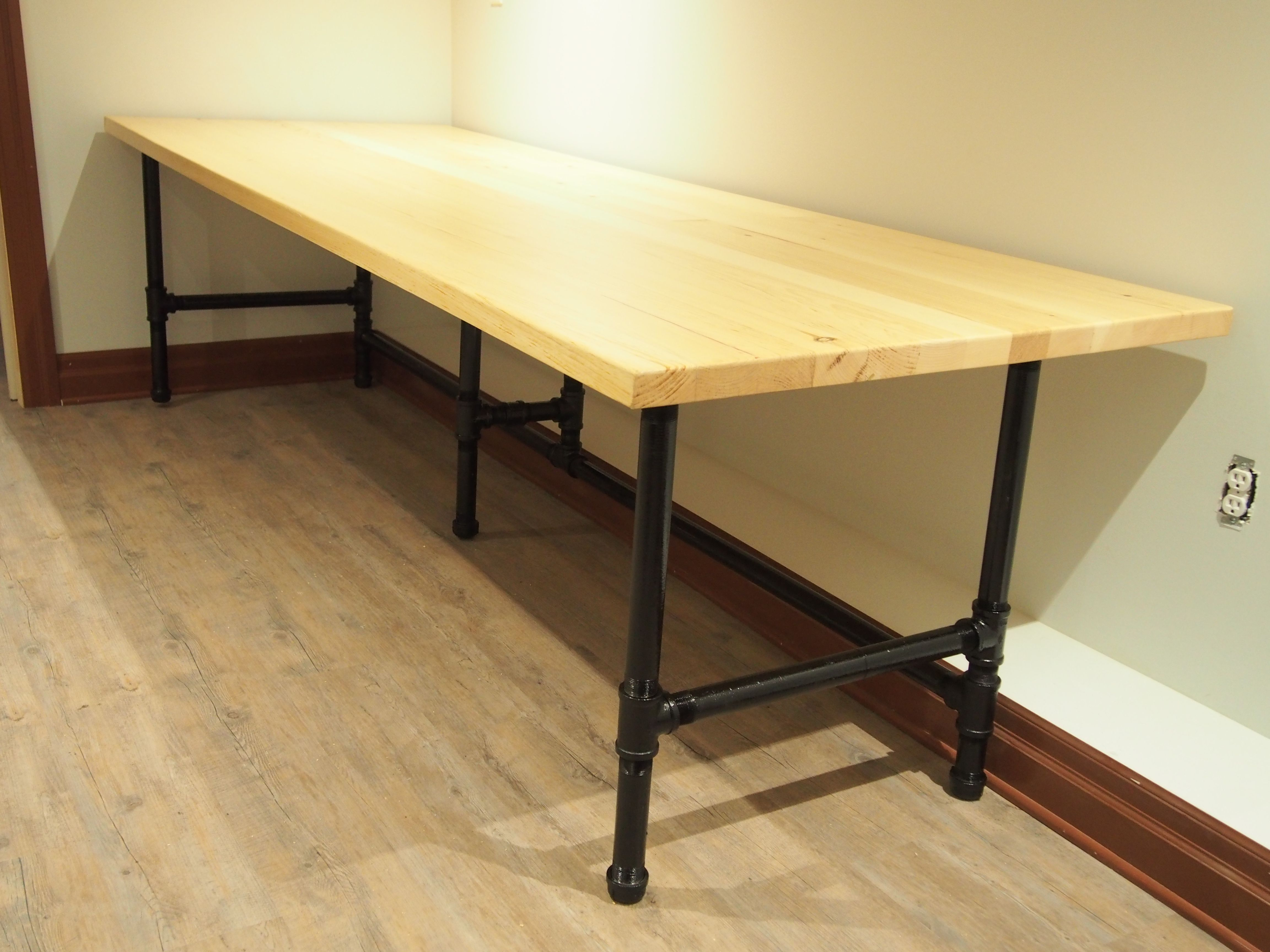 Long computer desk made with spare metal pipes and wood
