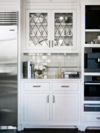 Glass-front cabinets hang above a subway tile backsplash ...