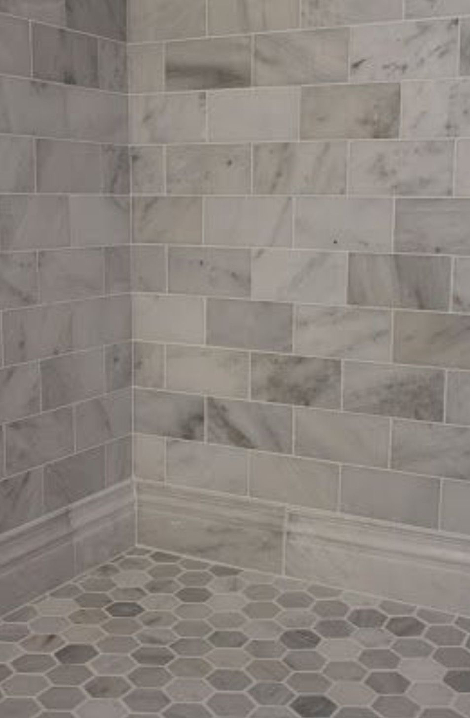 I like the baseboard tile large gray and white marble subway tile on shower wall and baseboard with a hexagon pattern on the floor
