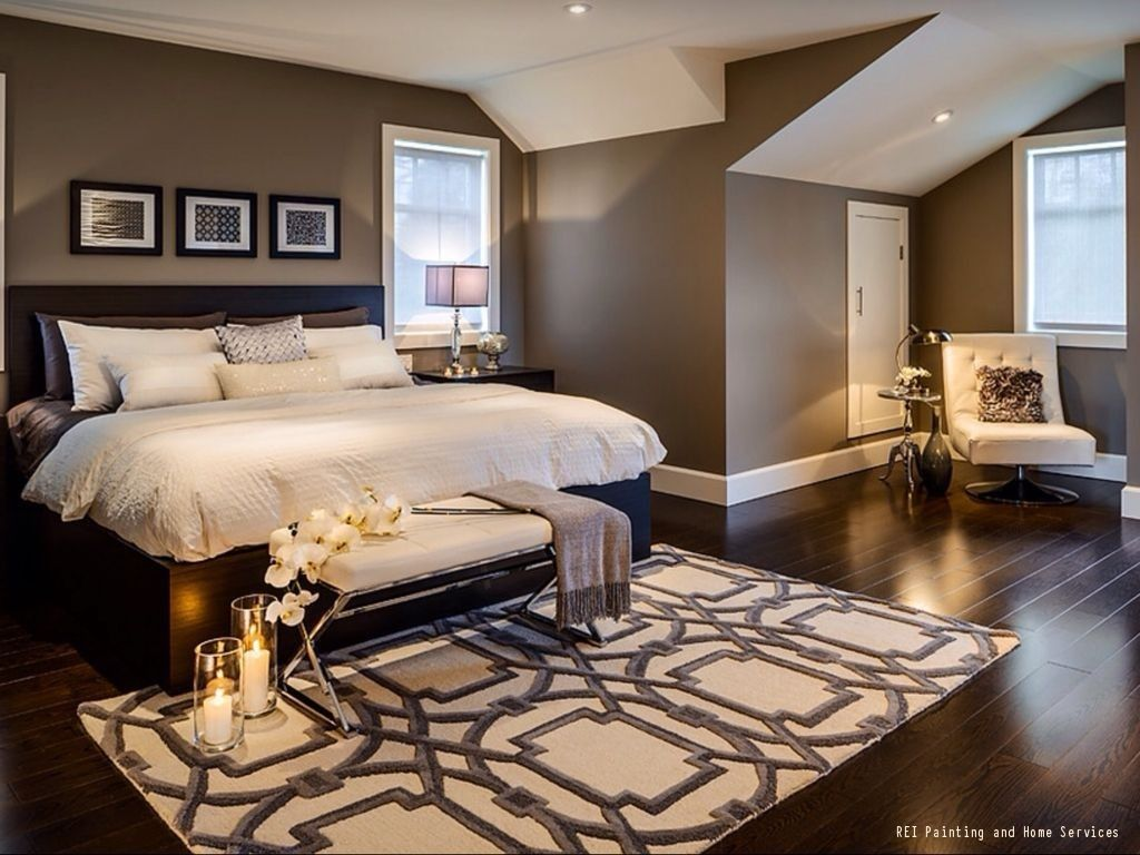 A warm and cozy bedroom with dark hardwood floors and brown paint the white ceiling
