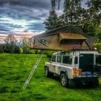 White Land Rover Defender with a Howling Moon roof tent