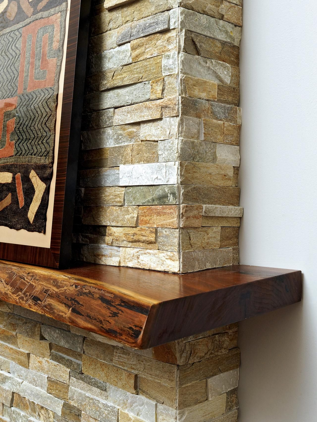 A live edge kitchen island in this contemporary home was the inspiration for incorporating live stone fireplace