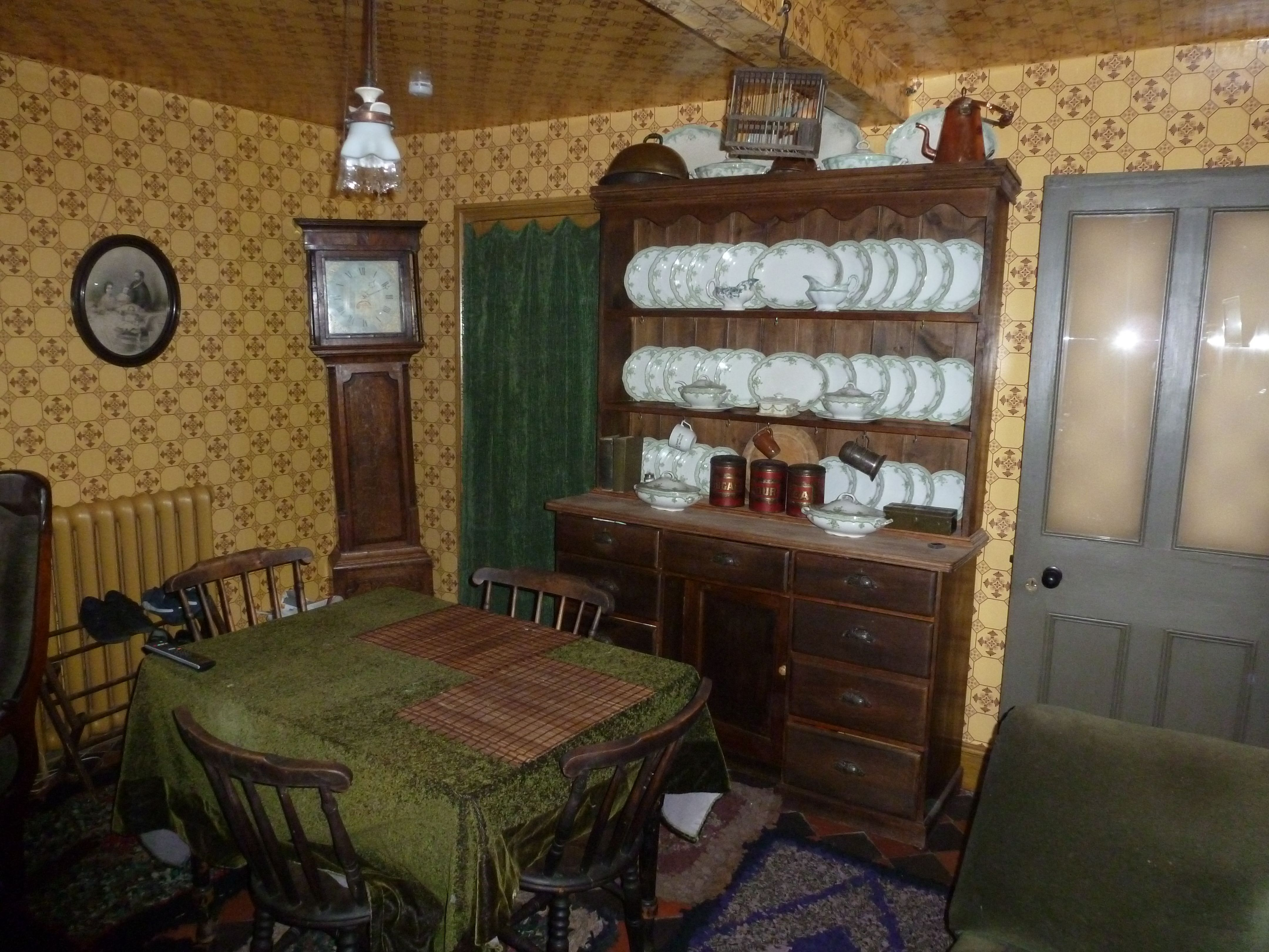 Recreation of working class living kitchen with reproduced sanitary wallpaper based on found fragements in the room and kitchen dresser in view