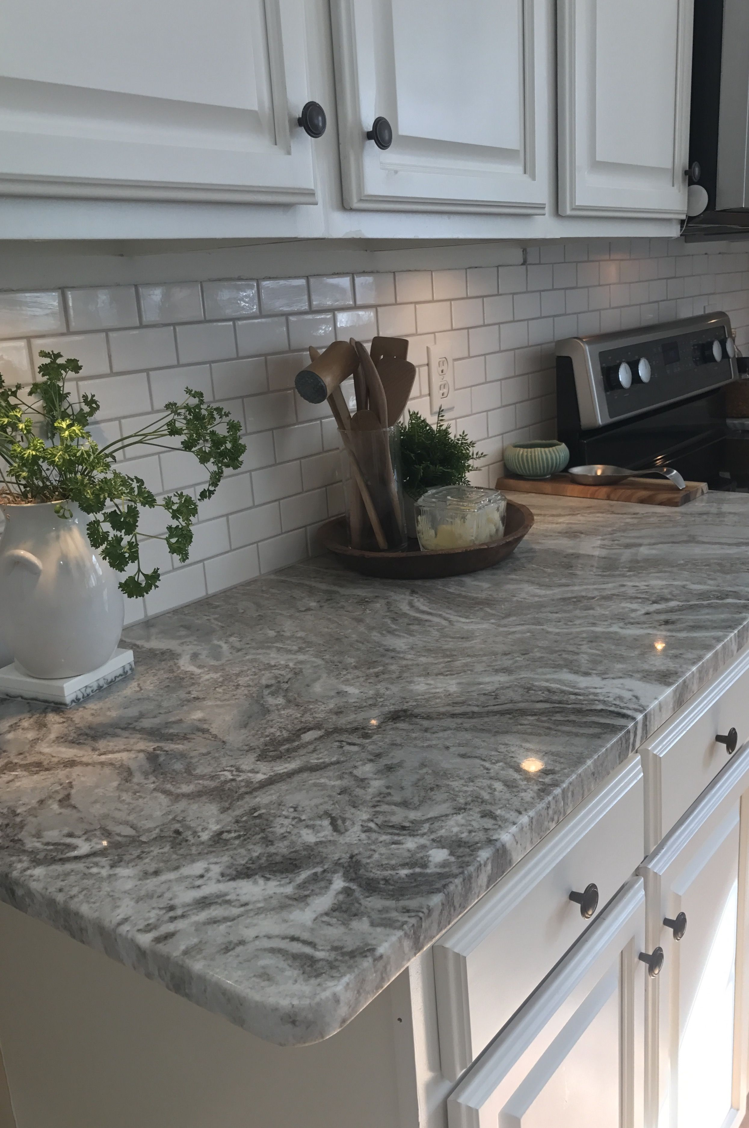 Fantasy brown granite with small white subway tiles and warm gray grout