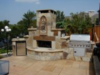 Outside kitchen with grills and vintage stone fireplace ...