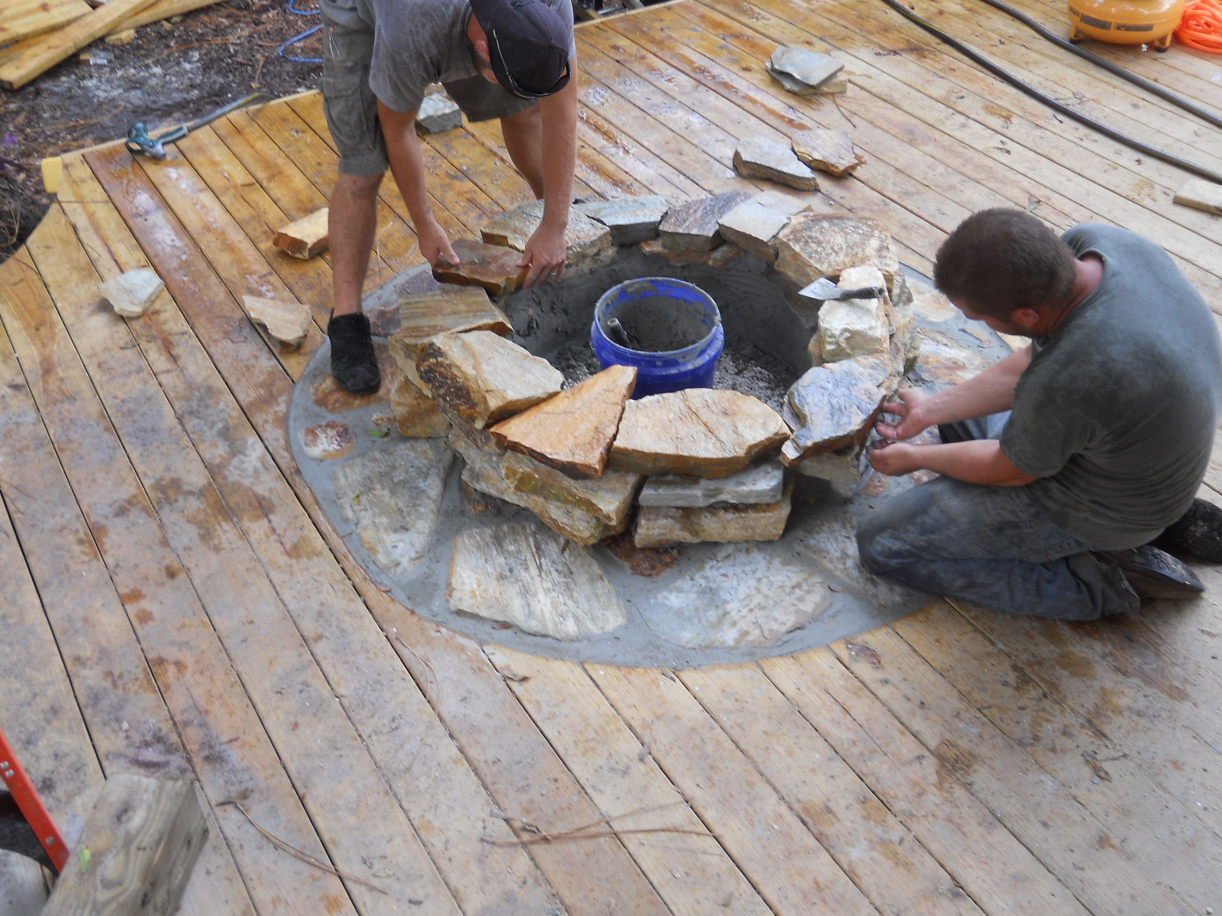 Craftsmen constructing a natural stone fire pit on wooden deck with stone inlay www