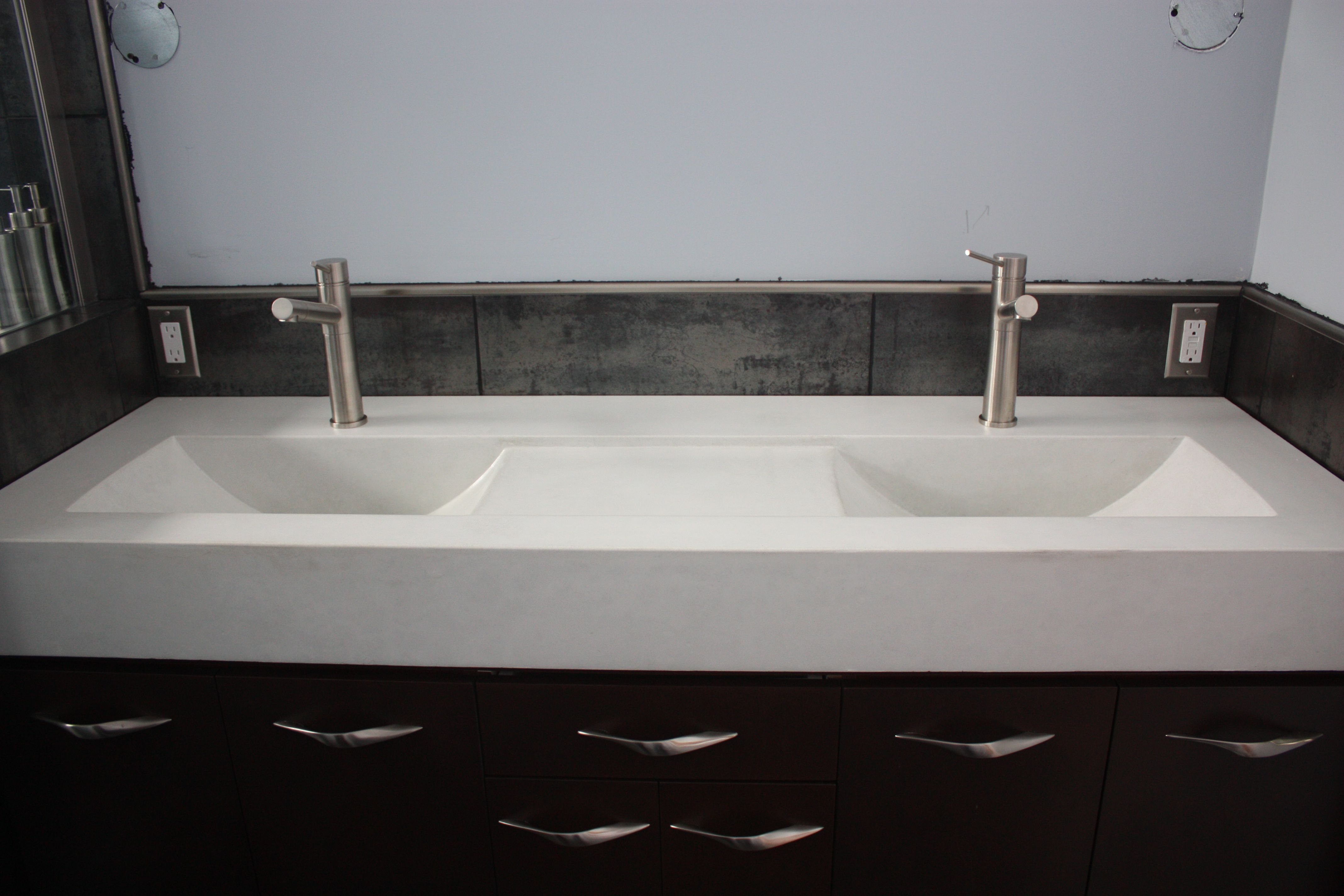 A double eclipse concrete vanity top the recessed area between the sinks is a cool
