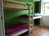 Triple bunk bed in room with low ceiling. Three frames and ...