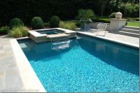 rectangular pool with tanning ledge and waterfall jacuzzi
