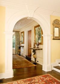 An elegantly trimmed arch connects the grand foyer with ...