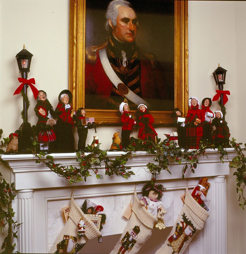 Carolers displayed on a mantle with garland and stockings - christmas carolers decorations