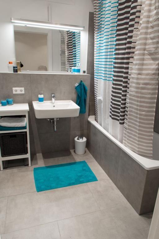 Graue Fliesen, graue Badewanne, blaue Akzente durch Teppich und - badezimmereinrichtung