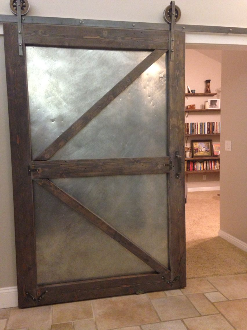 Industrial sliding barn door using aged sheet metal and