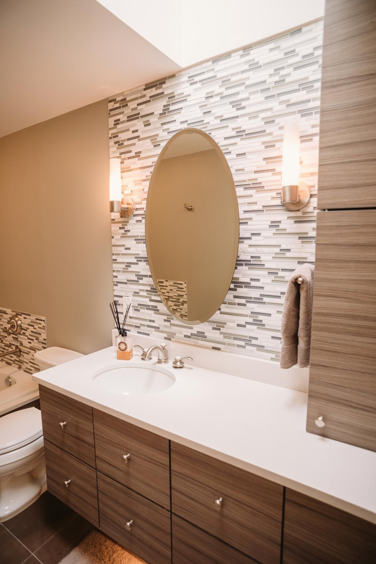 The attractive accent wall in this contemporary bathroom features thin tiles in white and neutral shades cylindrical sconces illuminate the space