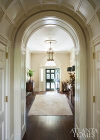 A grand foyer and center hall show off plaster molding, a ...