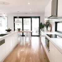 White open plan kitchen dining room with French doors ...
