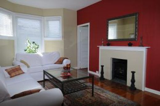 A cheerful living room featuring a bright red accent wall - accent wall in living room