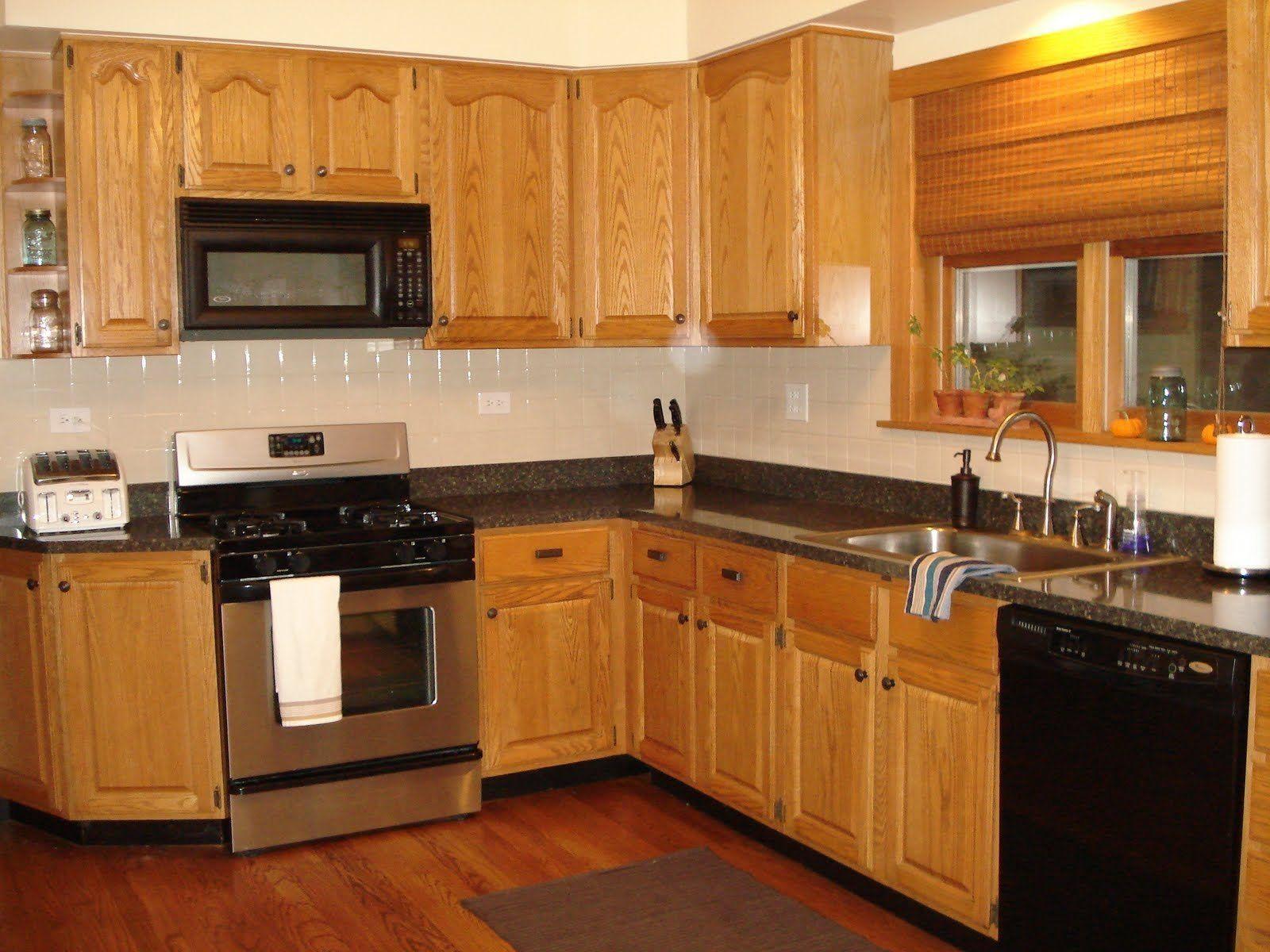 laminate flooring kitchen Kitchen white wall paint with brown wooden oak cabinet having black countertop on laminate flooring plus white tiles backsplash