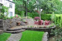 Tiered patio design sloping away from home with ...