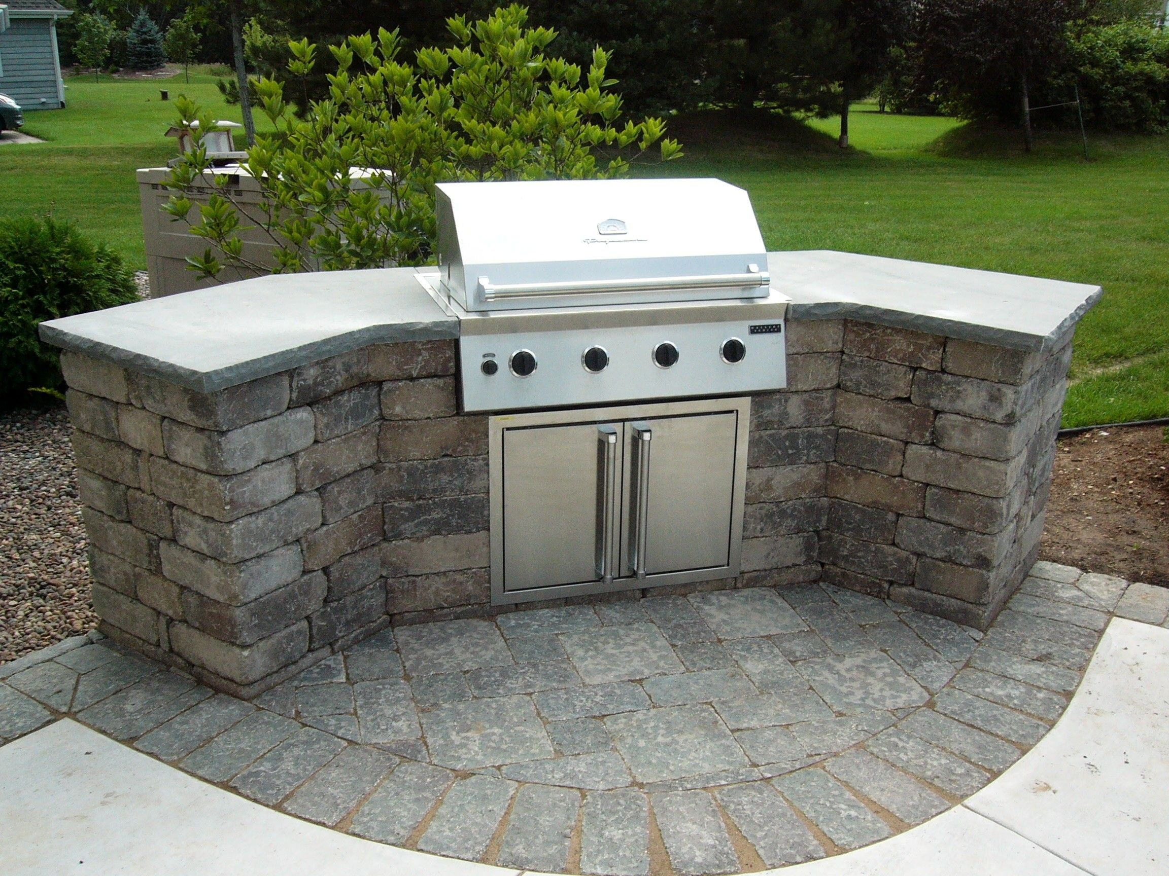 kitchen countertop material Curved Stone Prefab Kitchen Island With Gray Concrete Countertop And Barbeque Grill On Backyard Garden