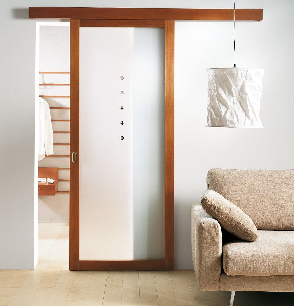 Modern interior sliding door featuring a walnut frame and acid etched decorative panel