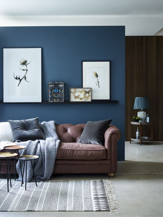 chic seating area with a brown sofa and a navy accent wall and - brown leather couch living room