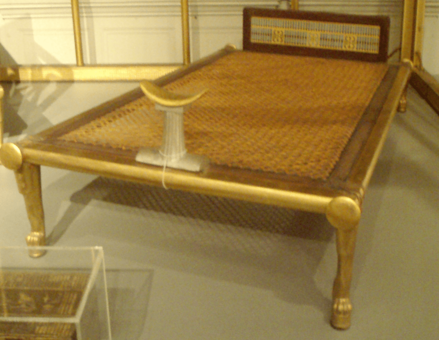 Ancient egyptian bed with a curved alabaster headrest standing where we would put a pillow
