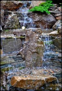 Moss rock and stacked stone waterfall display designed and ...