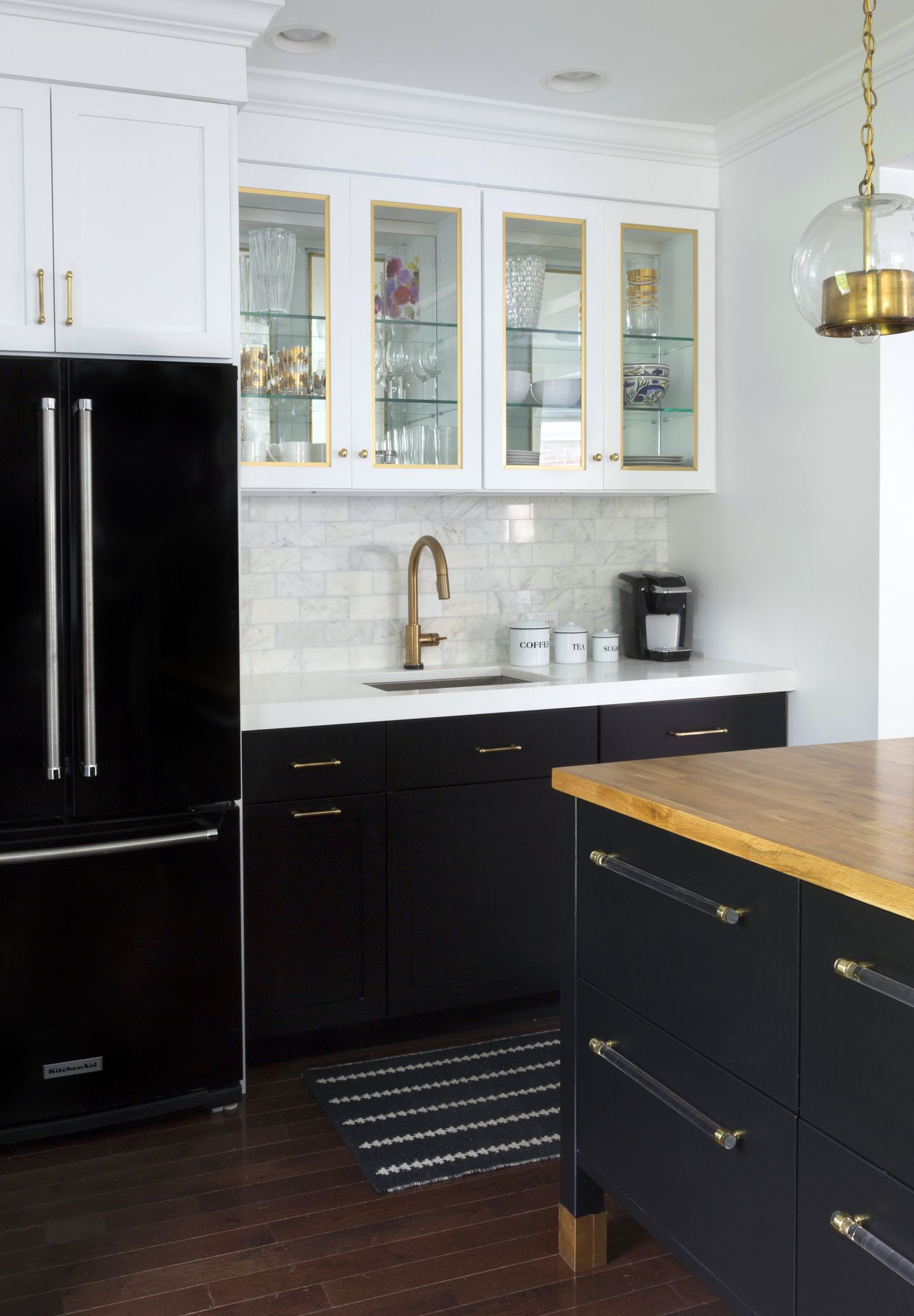 black kitchen cabinets Black refrigerator with black base cabinets and white upper cabinets marble subway tile brass hardware kitchen