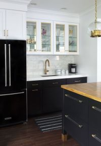 Black refrigerator with black base cabinets and white ...