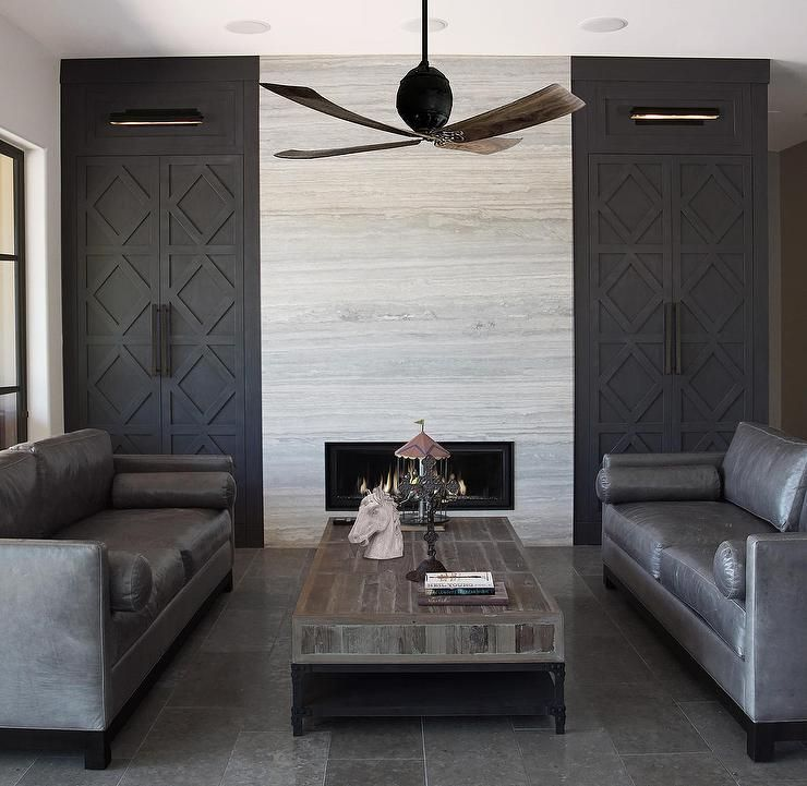 Contemporary living room features a ceiling fan over gunmetal gray - gray leather living room sets