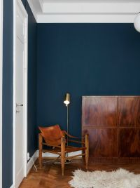 cozy corner with leather chair and a dark blue wall ...
